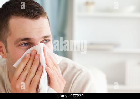 Homme malade soufflant son nez