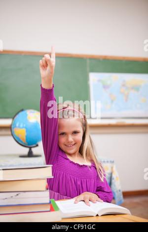 Portrait de jeune écolière levant la main Banque D'Images