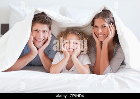 Happy Family posing sous une couette Banque D'Images