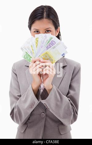 Businesswoman se cachant derrière l'argent Banque D'Images