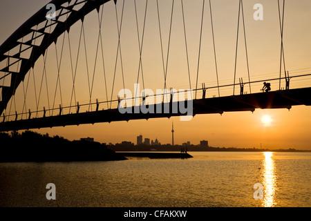 Cycliste traverse le pont piétonnier de la rivière Humber au lever du soleil avec Toronto Skyline in background, Banque D'Images