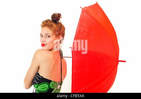 Portrait de jeune beauté frais fraise et mordant holding parapluie rouge, isolé Banque D'Images