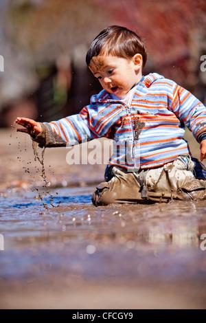 Un garçon de deux ans, joue dans une flaque de boue. Banque D'Images