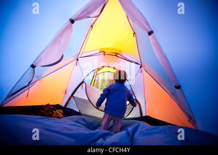 Un petit garçon s'ouvre et ferme la fermeture éclair tente pendant qu'il se tiennent sur un sac de couchage bleu. Banque D'Images