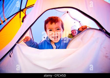 Un petit garçon s'ouvre et ferme la fermeture éclair tente pendant qu'il se dresse sur un sac de couchage bleu. La tente est orange et bleu. Le ca
