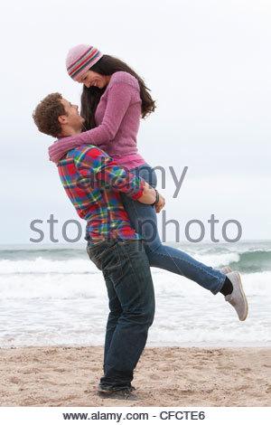 Jeune homme petite amie sur la plage de levage Banque D'Images