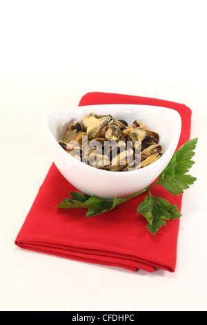 Moules marinées avec persil italien dans un bol sur fond lumineux Banque D'Images