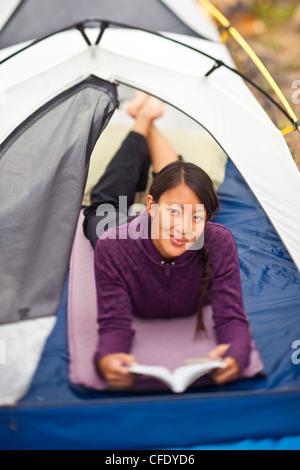 Une femme en bonne santé, heureux fait un peu de lecture tout en camping dans le parc national Jasper, Alberta, Canada