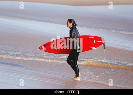 Surfer Girl sur la plage d'Estoril au Portugal Banque D'Images