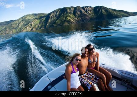Trois jeunes adultes rire et sourire alors qu'il était assis à l'arrière d'un bateau de wakeboard sur un lac dans Banque D'Images