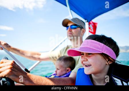 Les pilotes d'un homme un bateau ponton pendant que son fils de trois ans contribue à orienter, et sa fille de cinq ans s'assoit à côté d'eux, l'ours Lak