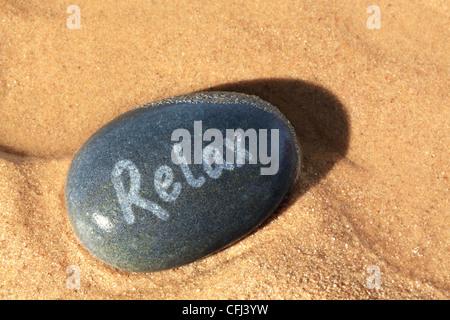 Photo d'un concept sur la plage de galets humides avec le mot vous détendre sur elle avec la fin de l'établissement Banque D'Images
