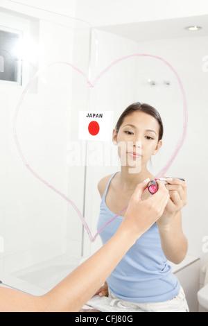 Young woman avec le rouge à lèvres sur le miroir Banque D'Images