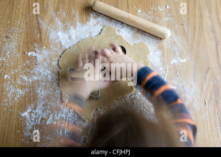 Little Boy making gingerbread men Banque D'Images