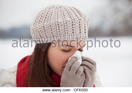 Une jeune femme debout dans la neige, s'être mouché le nez Banque D'Images