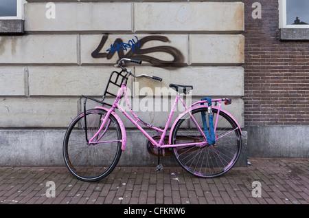 Vélo rose parqué par le mur à Amsterdam, Hollande