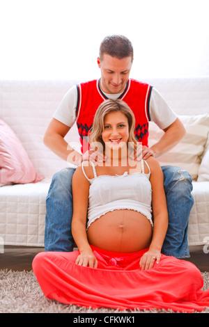 Jeune homme faisant sa femme enceinte massage Banque D'Images
