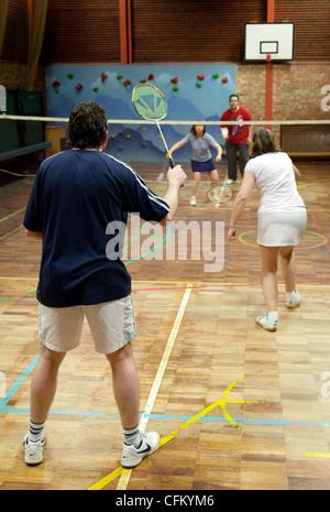 Les gens jouent à un jeu de double badminton à leur club local, Newmarket Suffolk UK Banque D'Images