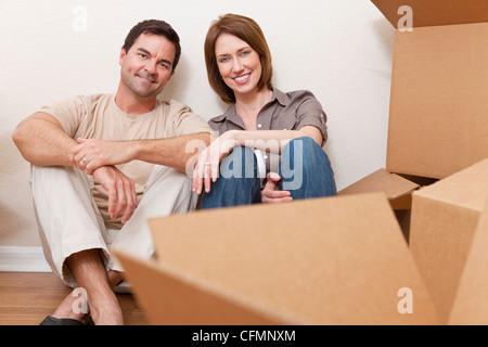 Heureux couple dans la trentaine se détendre lors du déballage ou boîtes d'emballage et de déménagement dans une Banque D'Images