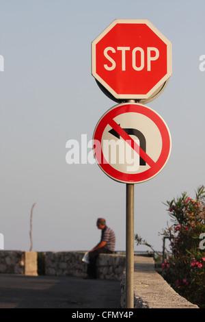 Un homme assis derrière un panneau routier. Dubrovnik, Croatie Banque D'Images
