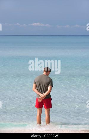 Homme debout à la cheville dans l'eau en contemplant l'océan, vue arrière Banque D'Images