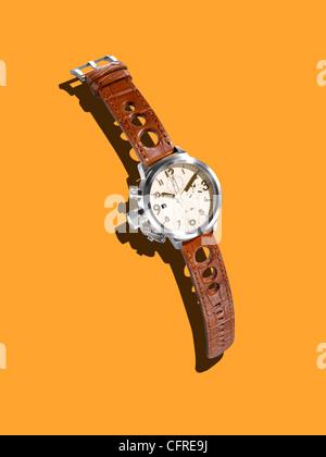 Une montre moderne avec un bracelet en cuir sur un fond de moutarde avec les créateurs de l'ombre. Banque D'Images