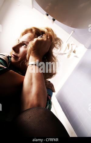 Femme assise sur la toilette. Banque D'Images