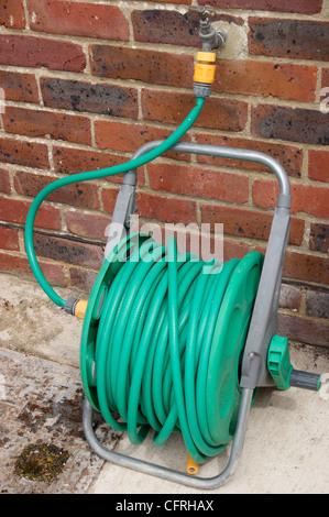 Tuyau flexible sur bobine fixée à l'extérieur sur le jardin avec arrosage dans l'interdiction en vigueur dans de Banque D'Images