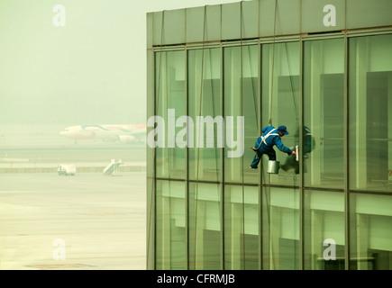 La pendaison window cleaner à l'aéroport de Beijing avec un avion sur l'arrière-plan, Chine Banque D'Images