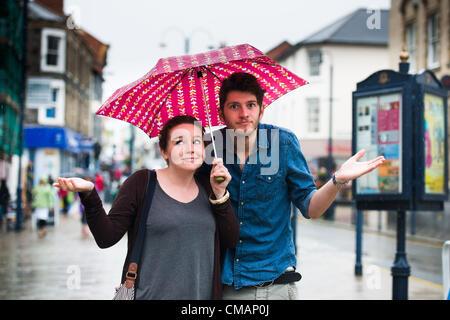 Aberystwyth, Pays de Galles, Royaume-Uni. Vendredi 6 Juillet 2012 Un jeune couple à Aberystwyth à l'abri de la pluie. L'Agence de l'environnement a émis des alertes Amber avertissement du risque d'inondation sur les rivières au Pays de Galles, et l'équivalent d'un mois de pluie est prévu à l'automne dans les régions du Royaume-Uni en seulement un jour. photo ©keith morris