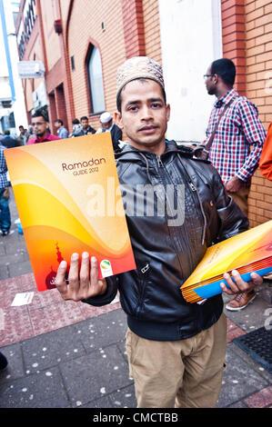 Londres, Royaume-Uni - 20 juillet 2012: un homme distribue le Ramadan 2012 Guide à l'extérieur de la mosquée est Banque D'Images