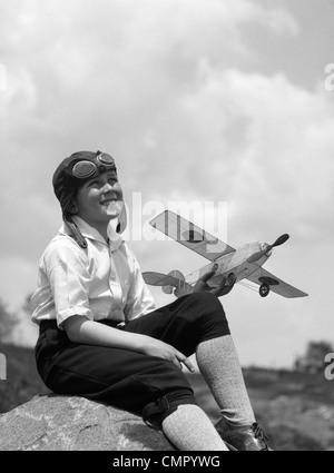 1930 garçon EN CUIR AVIATOR CAP AVEC LUNETTES ASSIS SUR LA ROCHE HOLDING MODEL PLANE Banque D'Images