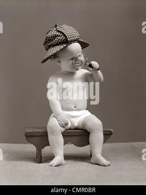 1940 BABY SHERLOCK HOLMES DANS L'ÉRYTHÈME ASSIS SUR UN BANC PORTANT DEER STALKER HAT À LA LOUPE À TRAVERS Banque D'Images