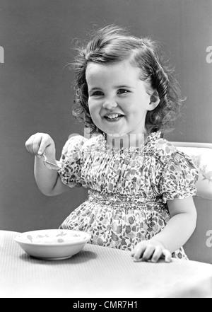 Années 1940 Années 1930 SMILING LITTLE GIRL EATING BOL DE CRÈME GLACÉE Banque D'Images
