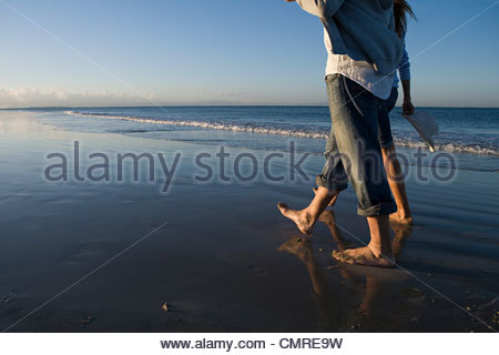 Couple en train de marcher au bord de la mer Banque D'Images