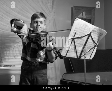1950 garçon dans la salle de séjour pratique de violon avec expression déterminée Banque D'Images