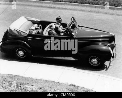 Années 1930 Années 1940 COUPLE MARI ET FEMME AU VOLANT CONVERTIBLE 1938 BERLINE QUATRE PORTES AVEC UNE ASSURANCE Banque D'Images
