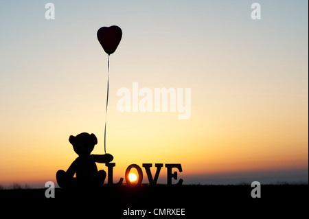 Ours en peluche tenant un ballon en forme de coeur trop suivant le mot amour au lever du soleil Banque D'Images