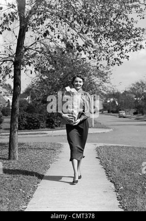 1950 FEMME MARCHE SUR TROTTOIR transportant un sac d'ÉPICERIE REMPLIS DE NOURRITURE Banque D'Images