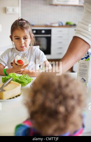 Enfants (2 à 7) et le père de prendre le petit déjeuner Banque D'Images