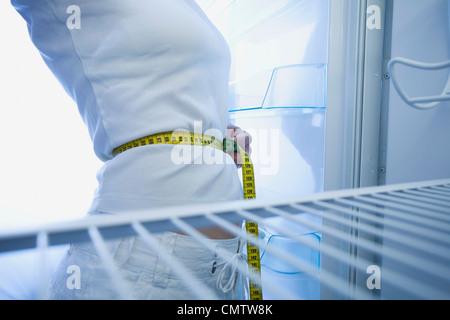 Femme avec ruban à mesurer autour de la taille Banque D'Images