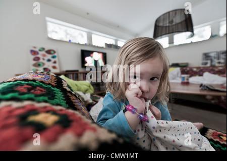 Jeune fille Blonde sucking thumb alors qu'elle repose sur le canapé Banque D'Images