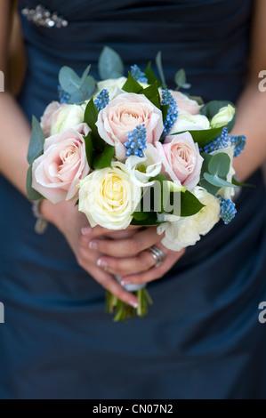 Femme dans une robe bleue tenant un bouquet de fleurs de printemps dont roses, muscari et ranunculus