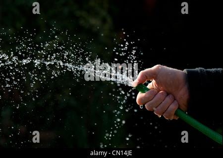 Pulvériser de l'eau avec le soutien de la main sur un fond sombre Banque D'Images