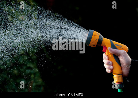 Jardiniers part pulvériser de l'eau avec le soutien de sur un fond sombre. UK Banque D'Images