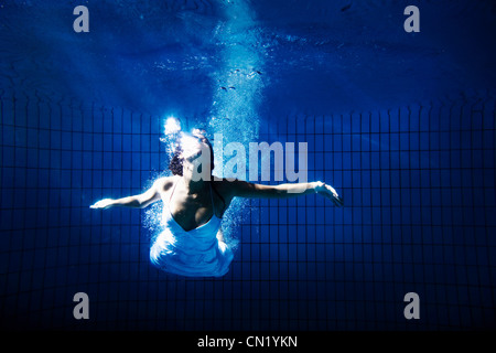 Femme en robe blanche sous l'eau Banque D'Images