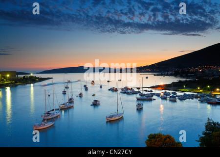 Voiliers par station d'vieille ville de Trogir en Dalmatie au coucher du soleil. Banque D'Images