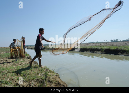 Pêche jeunes avec net dans la voie d'eau. Delta de l'Irrawaddy. Le Myanmar. Banque D'Images