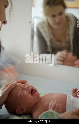 Bébé nouveau-né garçon pleurer, mother touching head Banque D'Images