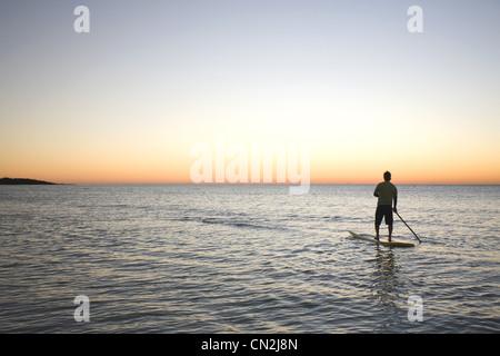 Man Paddleboarding sur l'océan au lever du soleil, Florida Keys, USA Banque D'Images